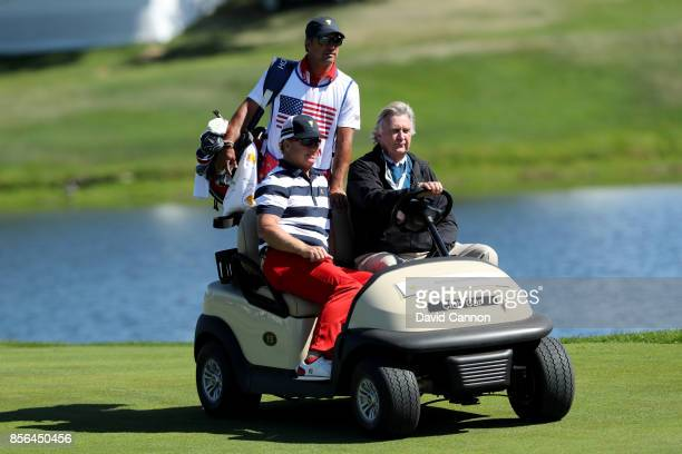 Charley Hoffman of the United States gets a ride with referee Mark Russell hole in his match against Jason Day of the International Team during the...