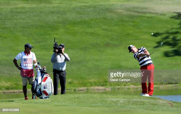 Charley Hoffman of the United States plays his third shot on the first hole in his match against Jason Day of the International Team during the final...