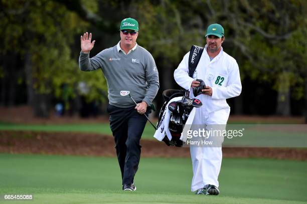Charley Hoffman of the United States waves as he approaches the 18th green alongside caddie Brett Waldman during the first round of the 2017 Masters...
