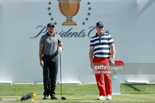 Charley Hoffman of the US Team watches his shot from the first tee as Jason Day of Australia and the International Team looks on during the Sunday...