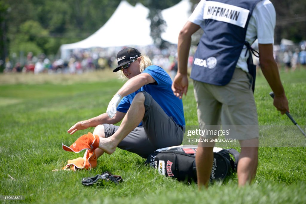 Charley Hoffman of United States dries his feet after chipping to the 4th green from a creek during the third round of the US Open at Merion Golf Club June 15, 2013 in Ardmore, Pennsylvania. AFP PHOTO/Brendan SMIALOWSKI