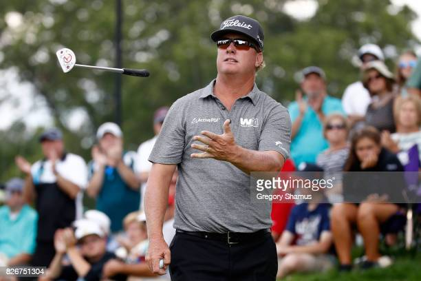 Charley Hoffman throws his putter to his caddie on the 12th green during the third round of the World Golf Championships Bridgestone Invitational at...