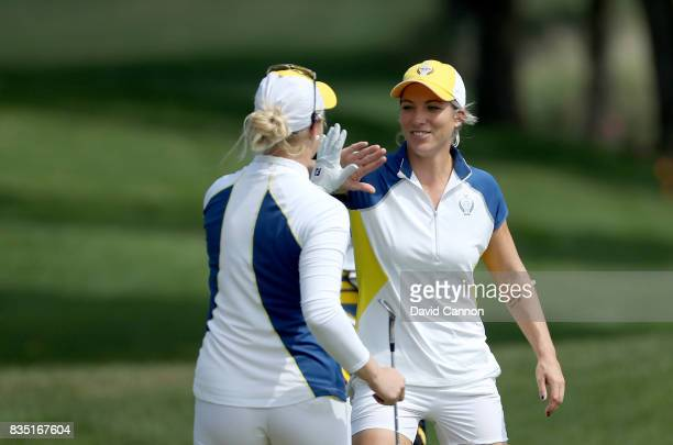 Charley Hull of England and the European Team celebrates with Melissa Reid after Hull had holed a chip shot to win the 16th hole in their match...