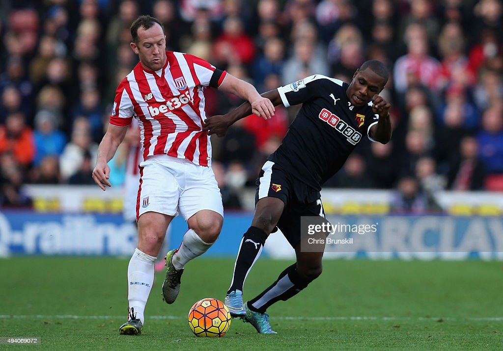 Charlie Adam of Stoke City and Odion Ighalo of Watford compete for the ball during the Barclays Premier League match between Stoke City and Watford at Britannia Stadium on October 24, 2015 in Stoke on Trent, England.