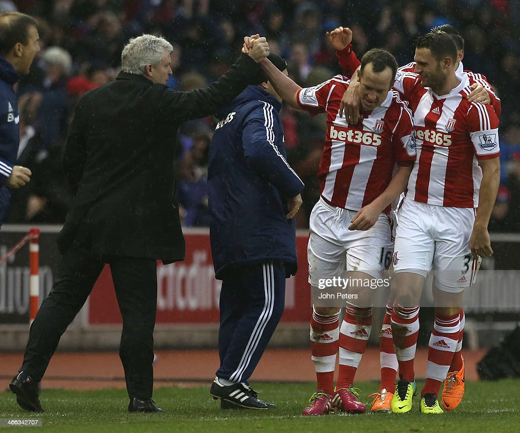 Charlie Adam (C) of Stoke City celebrates scoring their second goal with his manager Mark Hughes during the Barclays Premier League match between Stoke City and Manchester United at Britannia Stadium on February 1, 2014 in Stoke on Trent, England.