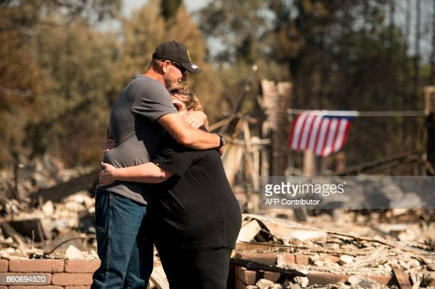 Charlie and Kate Higgins embrace in front of their burned home in Santa Rosa California on October 12 2017 Hundreds of people are still missing in...