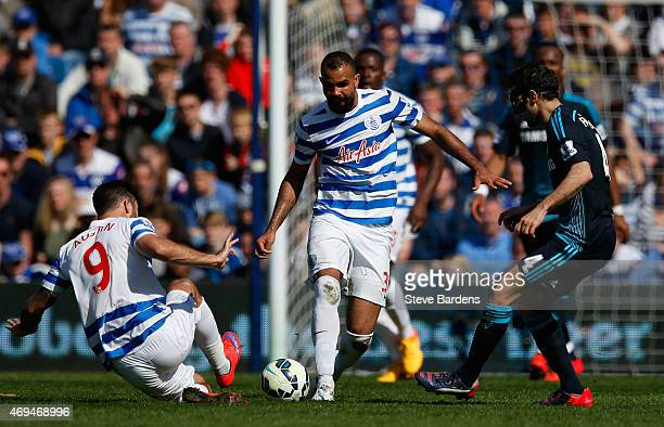 Charlie Austin and Sandro of QPR and Cesc Fabregas of Chelsea compete for the ball during the Barclays Premier League match between Queens Park...