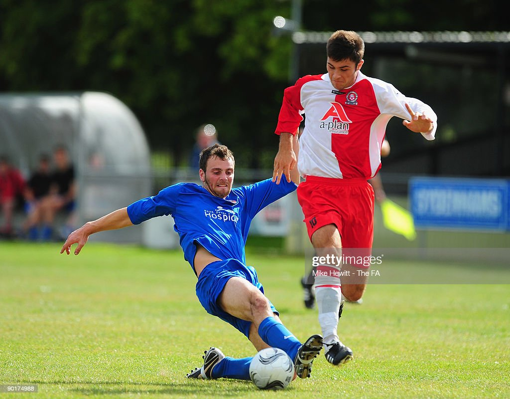 Charlie Austin of Poole Town gets through the tackle of Barnstable defender Steve Shore during the FA Cup Preliminary Round match between Poole Town...