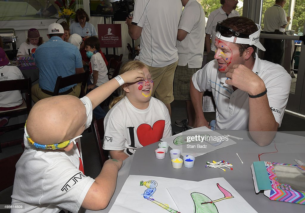 Charlie Beljan (R) watches two young patients from St. Jude Children's Research Hospital during the PGA TOUR Wives Association Art Party at during the Pro-Am round of the FedEx St. Jude Classic at TPC Southwind on June 4, 2014 in Memphis, Tennessee.
