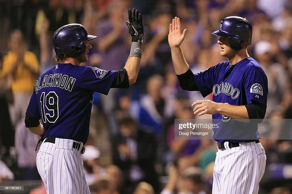 Charlie Blackmon #19 and <a gi-track='captionPersonalityLinkClicked' href=/galleries/search?phrase=DJ+LeMahieu&family=editorial&specificpeople=5940806 ng-click='$event.stopPropagation()'>DJ LeMahieu</a> #9 of the Colorado Rockies celebrate as they score on a two RBI single by Michael Cuddyer #3 of the Colorado Rockies off of Brandon Workman #67 of the Boston Red Sox in the seventh inning at Coors Field on September 24, 2013 in Denver, Colorado.