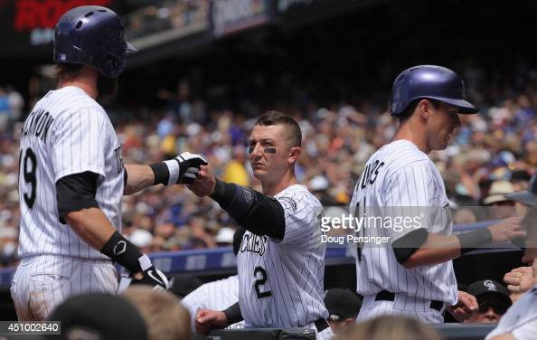 Charlie Blackmon and Drew Stubbs of the Colorado Rockies celebrate with Troy Tulowitzki of the Colorado Rockies after scoring on a single by Justin...