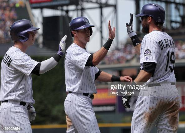 Charlie Blackmon and Drew Stubbs of the Colorado Rockies celebrate after scoring on a single by Justin Morneau of the Colorado Rockies off of...
