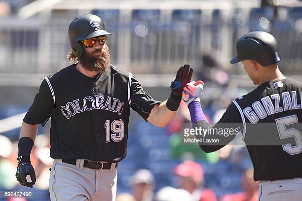 Charlie Blackmon of the Colorado Rockies celebrates a solo home run in the third inning with Carlos Gonzalez during a baseball game against the...
