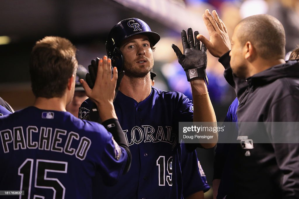 Charlie Blackmon #19 of the Colorado Rockies celebrates in the dugout after scoring on a two RBI single by Michael Cuddyer #3 of the Colorado Rockies off of Brandon Workman #67 of the Boston Red Sox in the seventh inning at Coors Field on September 24, 2013 in Denver, Colorado.