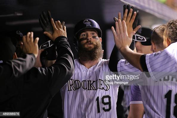 Charlie Blackmon of the Colorado Rockies celebrates in the dugout after scoring on a single by Nolan Arenado of the Colorado Rockies as the...