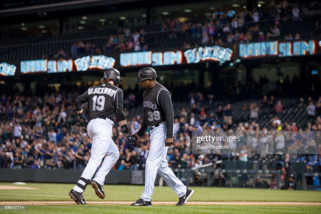 Charlie Blackmon #19 of the Colorado Rockies celebrates with third base coach Stu Cole #39 after hitting a seventh inning grand slam against the Cincinnati Reds at Coors Field on May 31, 2016 in Denver, Colorado.