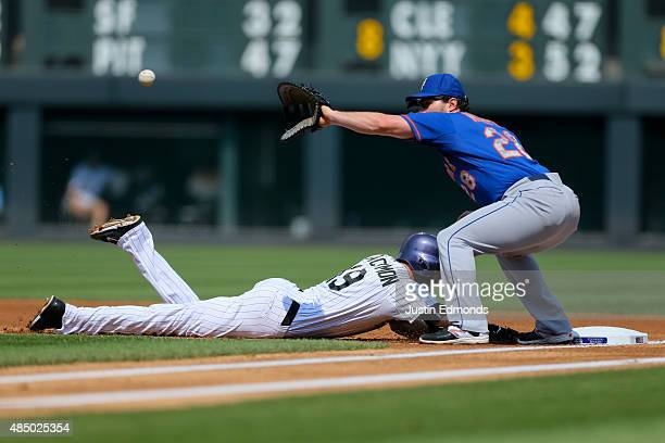 Charlie Blackmon of the Colorado Rockies dives safely back into first base as Daniel Murphy of the New York Mets receives the throw during the first...