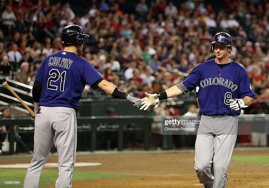 Charlie Blackmon #8 of the Colorado Rockies high fives Tyler Colvin #21 after scoring against the Arizona Diamondbacks during the fourth inning of the MLB game at Chase Field on October 3, 2012 in Phoenix, Arizona.