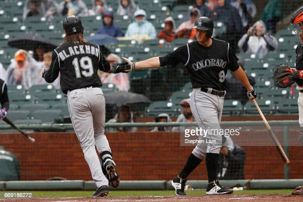 Charlie Blackmon of the Colorado Rockies is being congratulated by teammate DJ LeMahieu after hitting a leadoff home run during the first inning...