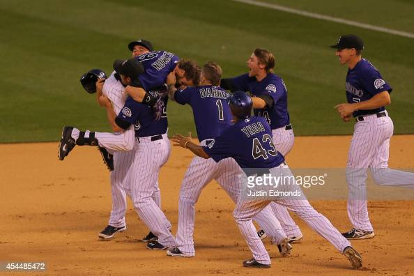 Charlie Blackmon of the Colorado Rockies is mobbed by teammates after hitting an RBI single for the walkoff 109 victory against the San Francisco...
