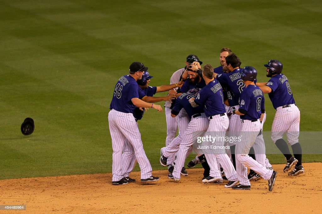<a gi-track='captionPersonalityLinkClicked' href=/galleries/search?phrase=Charlie+Blackmon&family=editorial&specificpeople=7519880 ng-click='$event.stopPropagation()'>Charlie Blackmon</a> #19 of the Colorado Rockies is mobbed by teammates after hitting an RBI single for the walk-off 10-9 victory against the San Francisco Giants at Coors Field on September 1, 2014 in Denver, Colorado.
