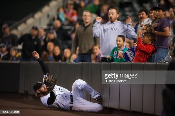 Charlie Blackmon of the Colorado Rockies makes a sliding catch in foul territory for an eighth inning out against the San Diego Padres at Coors Field...
