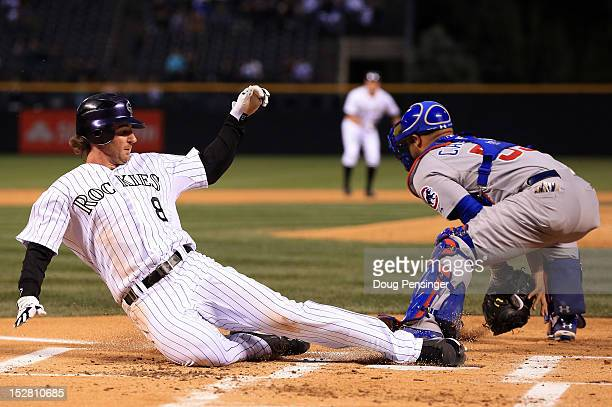 Charlie Blackmon of the Colorado Rockies slides home to score as catcher Welington Castillo of the Chicago Cubs takes the throw on double by Jordan...