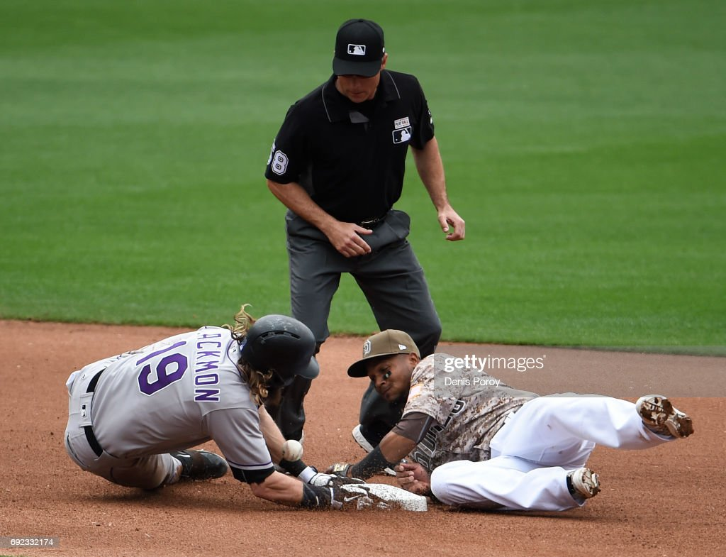 Charlie Blackmon #19 of the Colorado Rockies slides into second base with a double as Erick Aybar #8 of the San Diego Padres loses the ball as umpire Dan Iassogna looks on during the seventh inning of a baseball game at PETCO Park on June 4, 2017 in San Diego, California.
