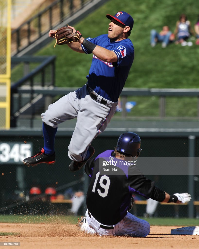 Charlie Blackmon #19 of the Colorado Rockies slides under a leaping Ian Kinsler #5 of the Texas Rangers at Salt River Field on February 25, 2013 in Scottsdale, Arizona.