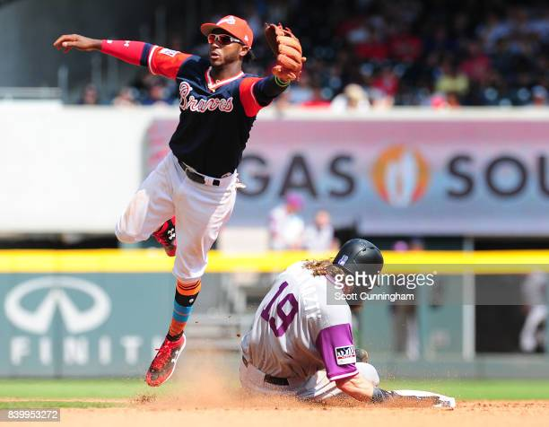 Charlie Blackmon of the Colorado Rockies steals second base as Ozzie Albies misses a throwing error by Kurt Suzuki against the Atlanta Braves at...