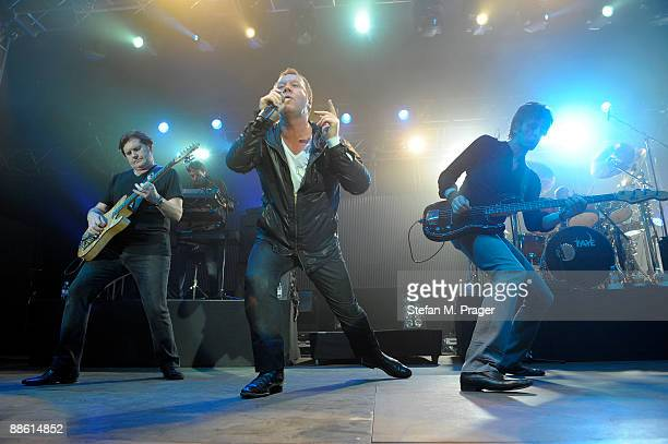Charlie Burchill Jim Kerr and Eddie Duffy of Simple Minds perform on stage as part of Tollwood festival at Olympic Park Grounds on June 20 2009 in...