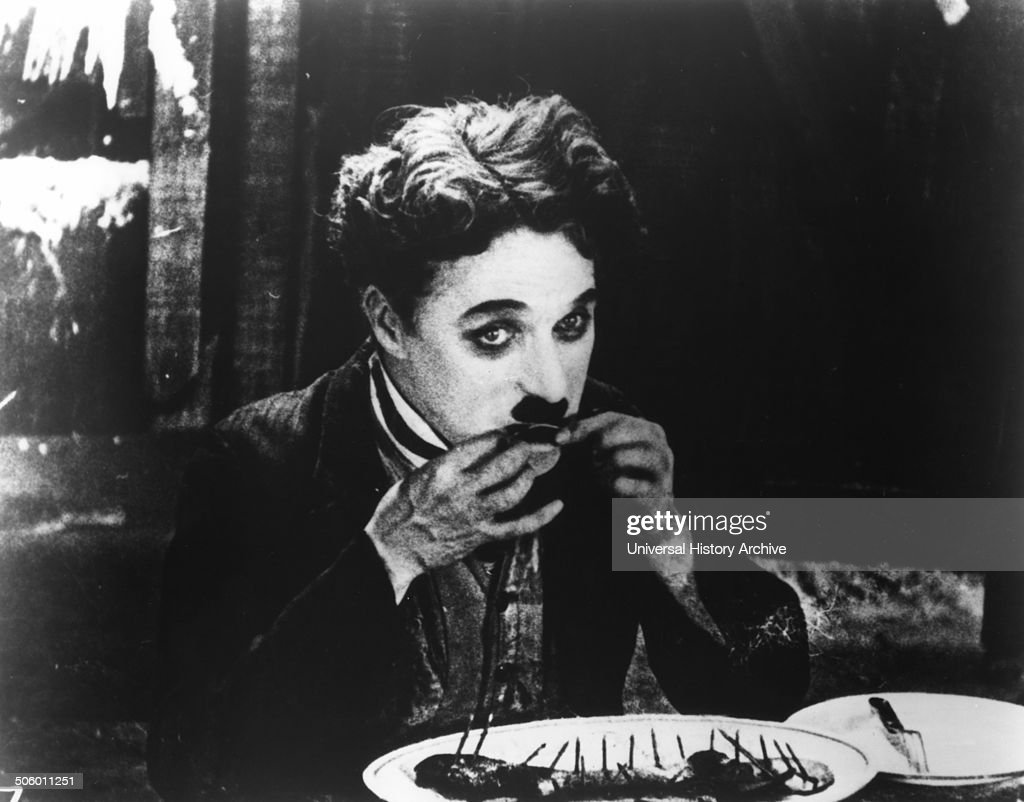 Charlie Chaplin, KBE (1889-1977). The Tramp resorts to eating his boot in a famous scene from The Gold Rush (1925).