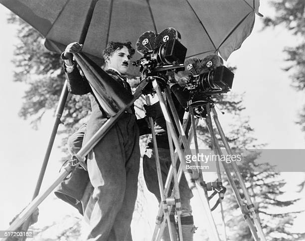Charlie Chaplin surveys the movie set from behind the cameras