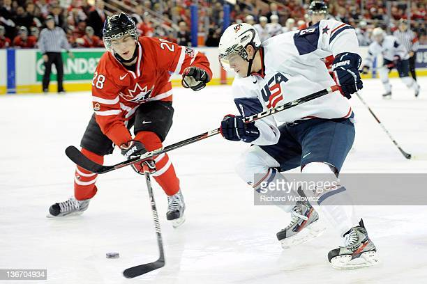 Charlie Coyle of Team USA skates with the puck while being defended by Nathan Beaulieu of Team Canada during the 2012 World Junior Hockey...