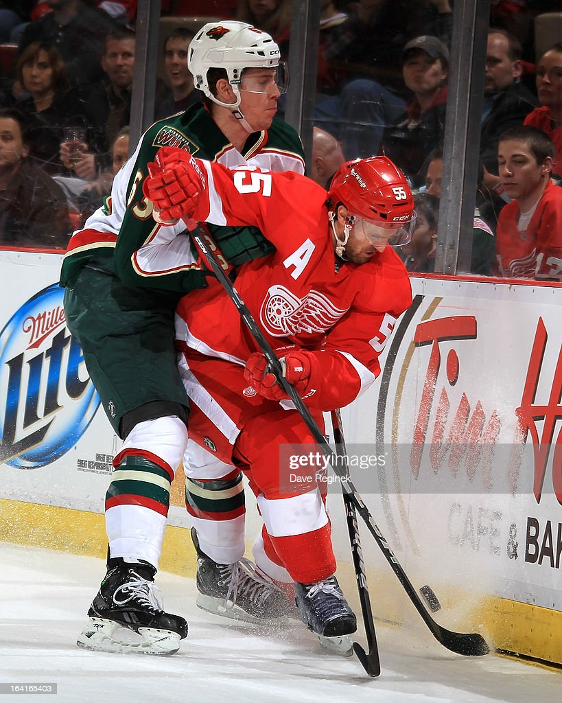 Charlie Coyle #63 of the Minnesota Wild and Niklas Kronwall #55 of the Detroit Red Wings go hard into the boards during a NHL game at Joe Louis Arena on March 20, 2013 in Detroit, Michigan.