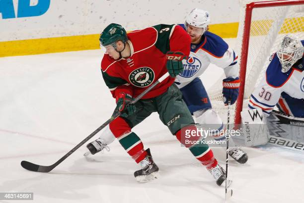 Charlie Coyle of the Minnesota Wild handles the puck with Jeff Petry of the Edmonton Oilers defending during the game on January 16 2014 at the Xcel...