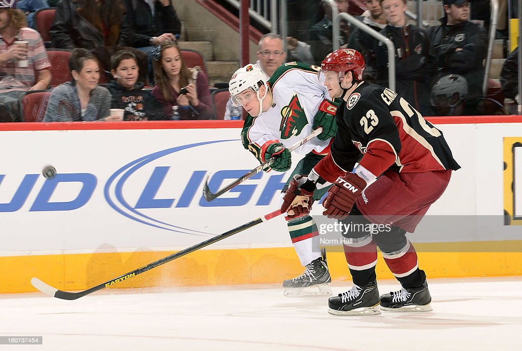 Charlie Coyle #63 of the Minnesota Wild passes the puck ahead of defenseman <a gi-track='captionPersonalityLinkClicked' href=/galleries/search?phrase=Oliver+Ekman-Larsson&family=editorial&specificpeople=5894618 ng-click='$event.stopPropagation()'>Oliver Ekman-Larsson</a> #23 of the Phoenix Coyotes during the third period at Jobing.com Arena on February 4, 2013 in Glendale, Arizona.