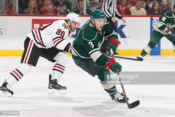 Charlie Coyle of the Minnesota Wild passes the puck with Brandon Saad of the Chicago Blackhawks defending in Game Four of the Western Conference...