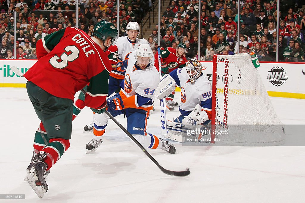 Charlie Coyle #3 of the Minnesota Wild shoots the puck with Calvin de Haan #44 and goalie Kevin Poulin #60 of the New York Islanders defending during the game on December 29, 2013 at the Xcel Energy Center in St. Paul, Minnesota.