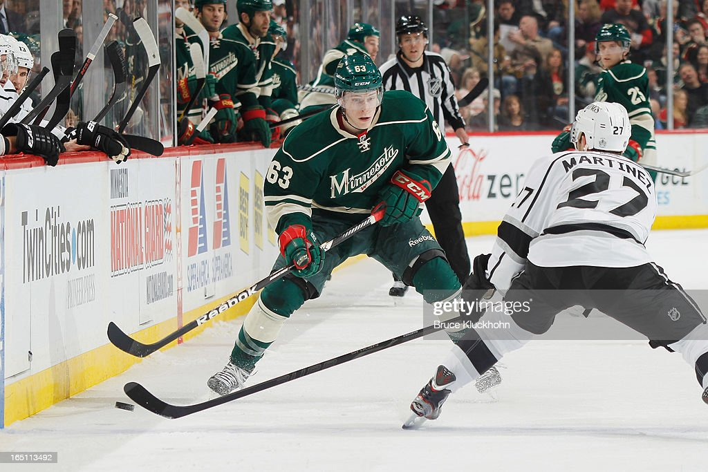 Charlie Coyle #63 of the Minnesota Wild skates with the puck while <a gi-track='captionPersonalityLinkClicked' href=/galleries/search?phrase=Alec+Martinez+-+Ice+Hockey+Player&family=editorial&specificpeople=5537193 ng-click='$event.stopPropagation()'>Alec Martinez</a> #27 of the Los Angeles Kings defends during the game on March 30, 2013 at the Xcel Energy Center in Saint Paul, Minnesota.
