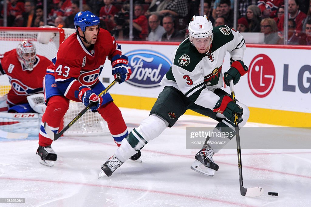 Charlie Coyle of the Minnesota Wild skates with the puck while being defended by Mike Weaver of the Montreal Canadiens during the NHL game at the...