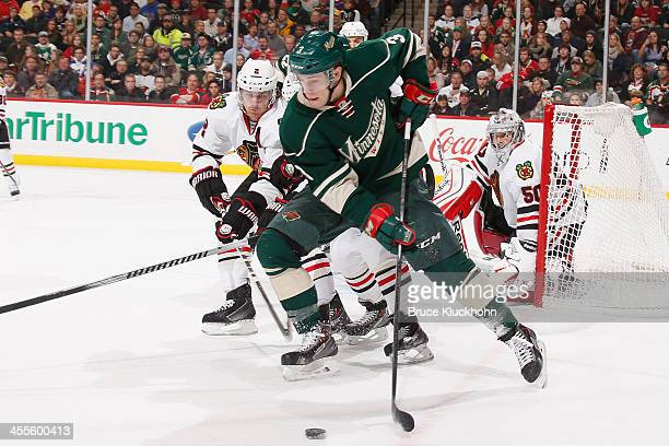 Charlie Coyle of the Minnesota Wild skates with the puck while Duncan Keith and Kris Versteeg of the Chicago Blackhawks defend during the game on...