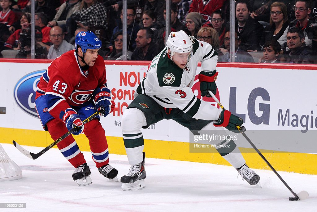 Charlie Coyle of the Minnesota Wild stick handles the puck in front of Mike Weaver of the Montreal Canadiens during the NHL game at the Bell Centre...
