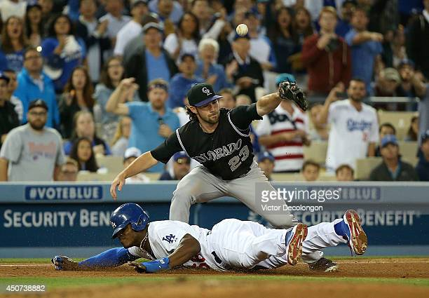 Charlie Culberson of the Colorado Rockies can't handle the throw to third base as Yasiel Puig of the Los Angeles Dodgers slides head first into third...