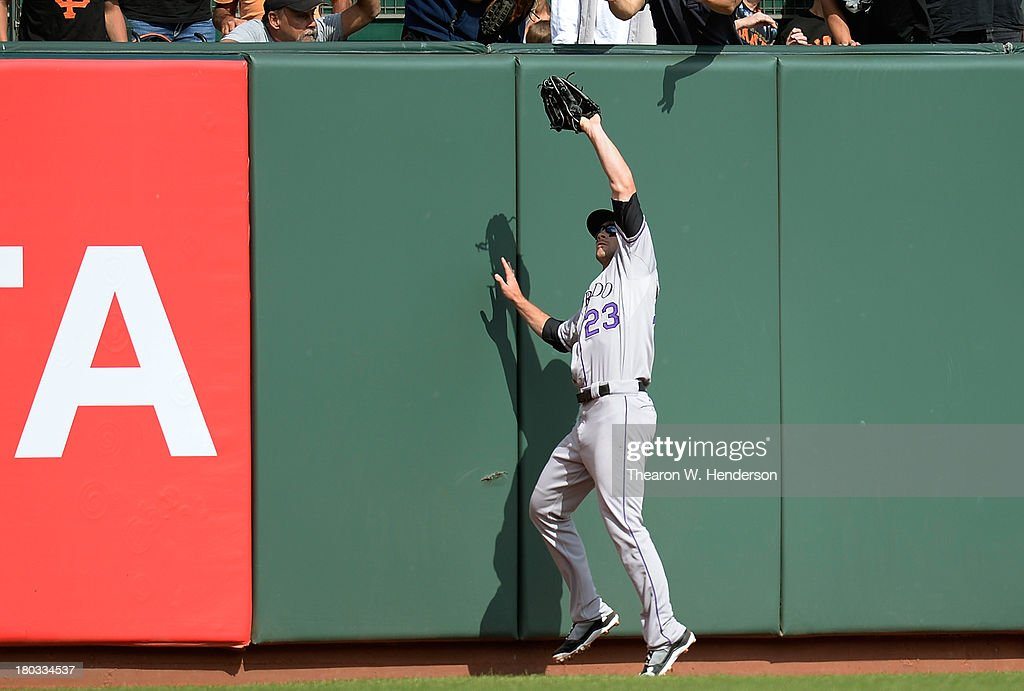 Charlie Culberson #23 of the Colorado Rockies catches this ball at the fence off the bat of Hunter Pence #8 of the San Francisco Giants during the seventh inning at AT&T Park on September 11, 2013 in San Francisco, California. The bases were loaded with no outs and Pence just missed hitting a grand slam home runl.