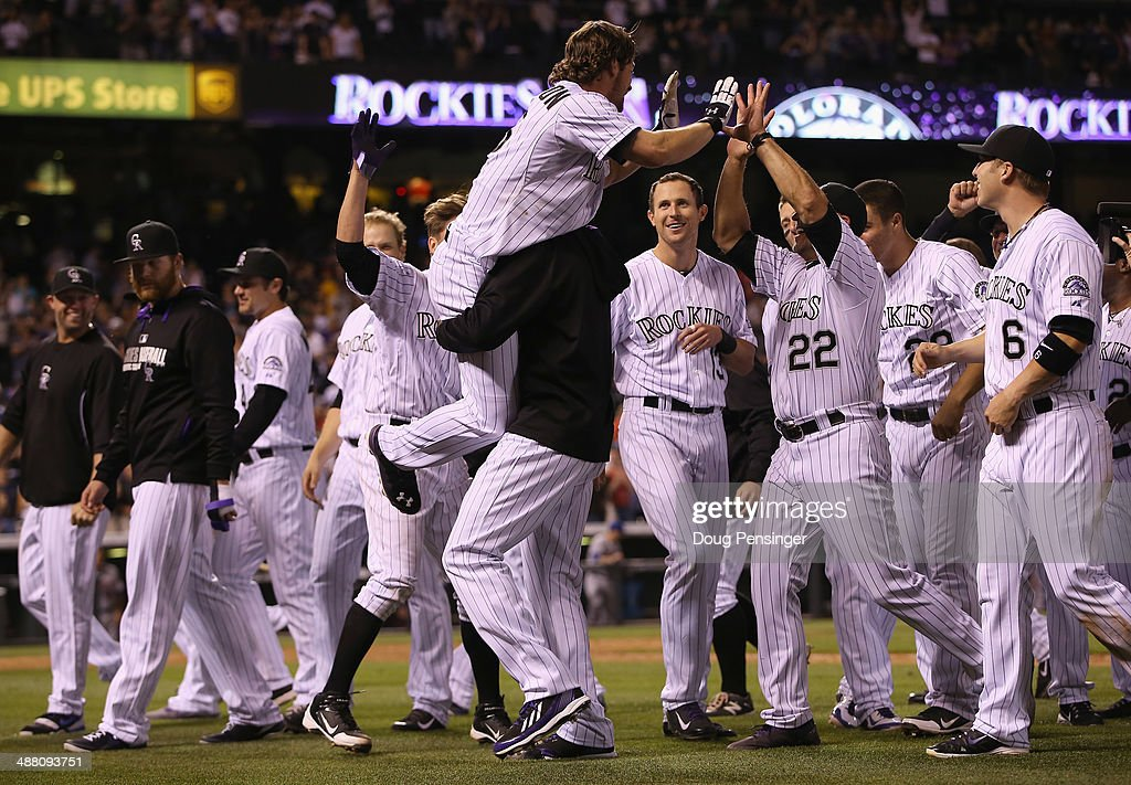 Charlie Culberson of the Colorado Rockies is hoisted in the air by winning pitcher LaTroy Hawkins of the Colorado Rockies as manager Walt Weiss and...