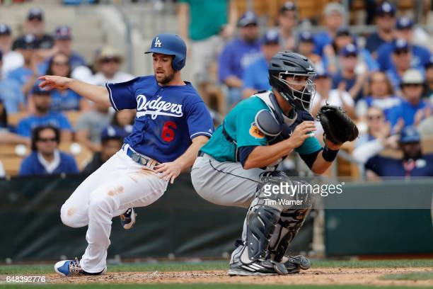 Charlie Culberson of the Los Angeles Dodgers slides into home as Nevin Ashley of the Seattle Mariners awaits the throw in the seventh inning of the...