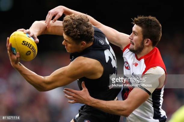 Charlie Curnow of the Blues and Joel Smith of the Demons compete for the ball during the 2017 AFL round 16 match between the Carlton Blues and the...