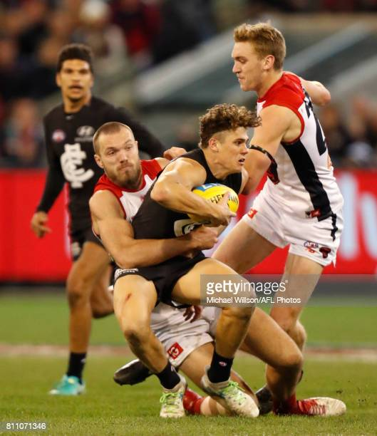 Charlie Curnow of the Blues is tackled by Max Gawn of the Demons during the 2017 AFL round 16 match between the Carlton Blues and the Melbourne...