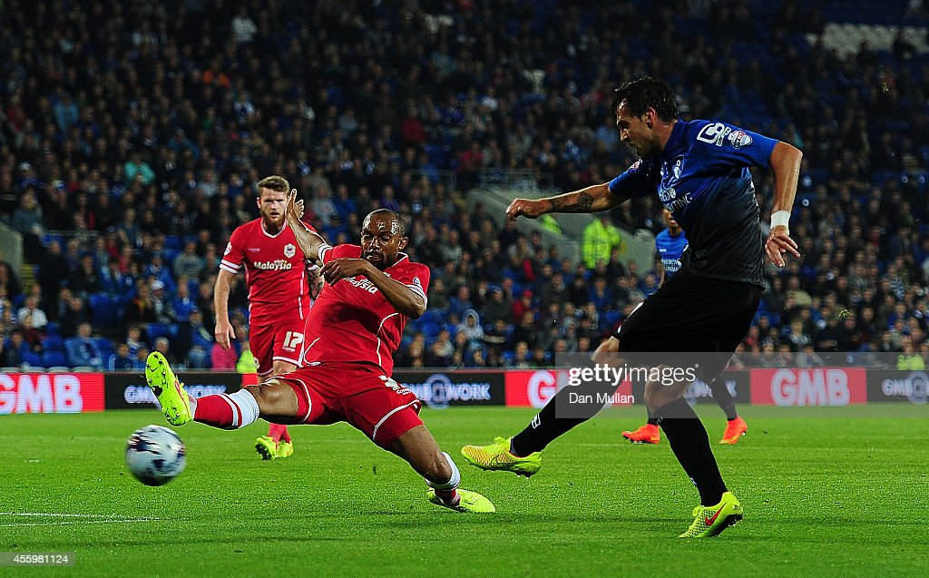 Charlie Daniels of Bournemouth (L) scores his side's second goal past Daniel Gabbidon of Cardiff City during the Capital One Cup third round match between Cardiff City and Bournemouth at Cardiff City Stadium on September 23, 2014 in Cardiff, Wales.